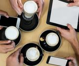 Friends using mobile phone and digital tablet while having cup of coff