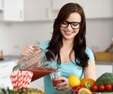 Happy healthy young woman wearing glasses pouring vegetable smoothies